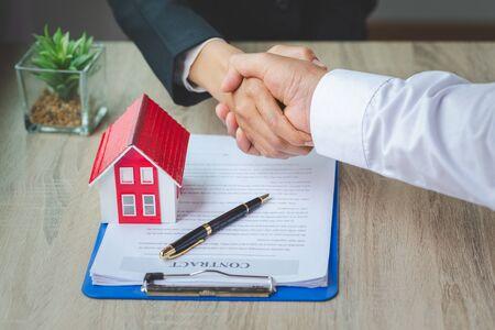 Agent immobilier serrant la main du client après la signature du contrat, entreprise signant un contrat d'achat - vente de maison, concept de maison à louer. Banque d'images