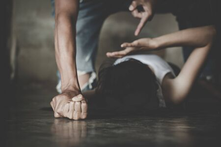 Scared abuse victim being attacked by a mad man in a dark place, Young woman subjecting to violence. Rape and sexually abused concepts. Foto de archivo