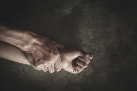 Man's hand holding a woman hand for rape and sexual abuse. Hands for rape and sexual abuse concept. Sexual abuse is a problem or Social issues concept.