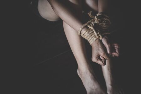 Kidnapped woman tied with rope, abused, hostage, victim woman in pain, Human trafficking, Human rights.