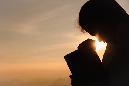 Silhouette of christian young woman praying with holy bible at sunrise, Christian Religion concept background. Reklamní fotografie