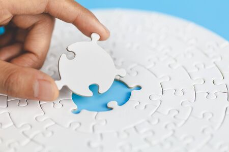 White jigsaw in the hands of humans, The correct solution. Teamwork, Solving and completing the task. Last piece of jigsaw puzzle. Assembling jigsaw puzzle pieces.