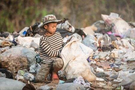 Poor boy collecting garbage in his sack to earn his livelihood, The concept of poor children and poverty Stock Photo