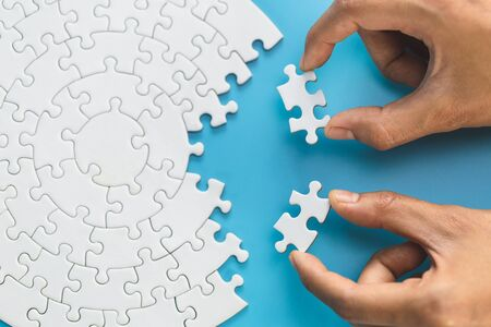 Hand put the last piece of jigsaw puzzle to complete the mission. Completing final task, missing jigsaw puzzle pieces and business concept with a puzzle piece missing. Standard-Bild