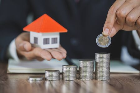 Real estate investors hold home models and money in hands. Saving plan to buy property, house. Personal financial concept for own a house. coin stack on wood table. copy space.