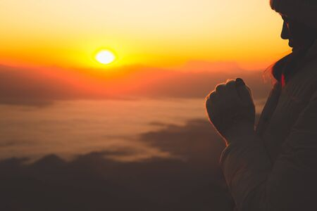 Man thank God on the mountain at sunrise in the morning,Praying for blessings from God in the morning.