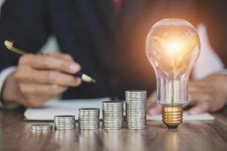business accounting with saving money with the growth of a pile of coins and light bulbs that illuminate. glowing light bulb among many coins heap business concept. Фото со стока