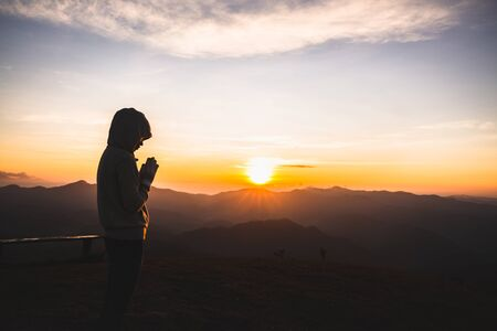 woman Praying hands with faith in religion and belief in God On the morning sunrise background. Namaste or Namaskar hands gesture, Pay respect, Prayer position.