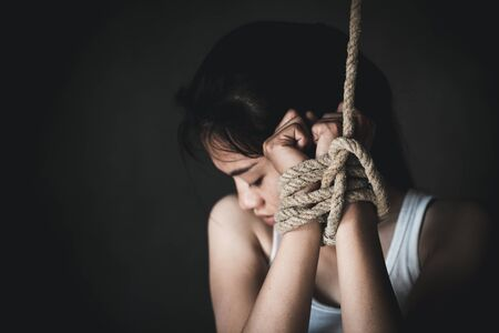 Hands of a missing kidnapped, abused, hostage, victim woman tied up with rope in emotional stress and pain, Human trafficking ,Stop abusing violence.