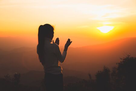 A women is praying to God on the mountain. Praying hands with faith in religion and belief in God on blessing background. Power of hope or love and devotion.