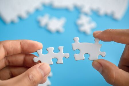 Business women connecting white jigsaw puzzles, , cooperation in decision making, team support in solving problems and corporate group teamwork concept.