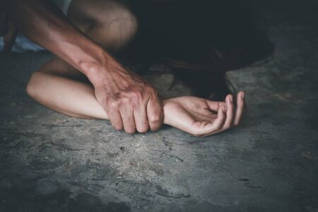 Close up of man hands holding a woman hands for rape and sexual abuse concept, Wound domestic violence rape, sexual assault, stop violence against women, human trafficking.