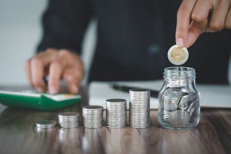 businessman holding coins putting in glass jar, step of coins stacks on working table, concept saving money for finance accounting.