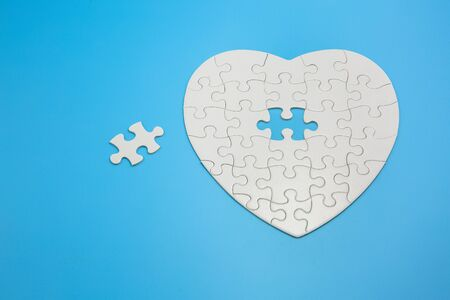 White heart shaped jigsaw puzzle on blue background with copy space. Business strategy teamwork and problem solving concept. Фото со стока