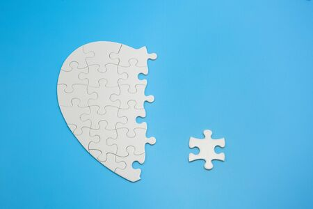 Unfinished white jigsaw puzzle pieces on blue background,  Copy space.