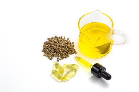 Hemp oil and pile of hemp seeds isolated on white background, top view. Pure cold pressed oils concept, CBD hemp oil.