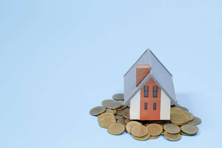 Model house on stack of coins on a blue background. Concept of Investment property, Real estate, Saving money.