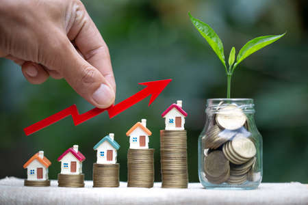 Hand  holding graph over the Increasing house miniature and trees that grow in glass bottles. Property investment and house mortgage financial concept, Investment property, Real estate, Saving money. 版權商用圖片 - 151351613