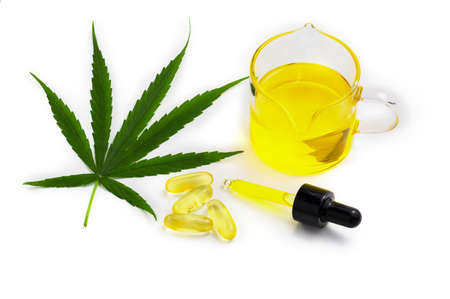 Hemp oil capsules and cannabis leaves on a white background, CBD hemp oil, medical marijuana concept.