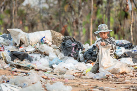 A poor boy collecting garbage waste from a landfill site. Concept of livelihood of poor children.Child labor.
