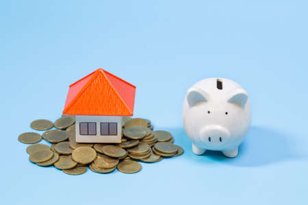 House on the coin and Piggy bank On a blue background,  planning savings money of coins to buy a home, property ladder, mortgage and real estate investment.  saving or investment for a house