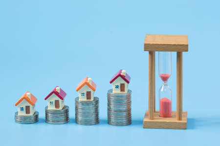 House on the coin  On a blue background,  planning savings money of coins to buy a home, property ladder, mortgage and real estate investment.  saving or investment for a house
