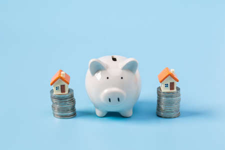 House on the coin and Piggy bank On a blue background,  planning savings money of coins to buy a home, property ladder, mortgage and real estate investment.  saving or investment for a house 版權商用圖片 - 151710847