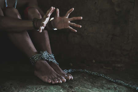 Hopeless man hands tied together with chain, Victims of human trafficking