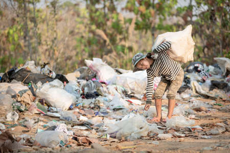 A poor boy collecting garbage waste from a landfill site in the outskirts. Poverty and child labor concept, human trafficking. 版權商用圖片 - 152257075