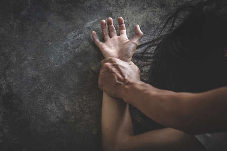 Man's hand holding a woman hand for rape, Stop sexual harassment and violence against women.