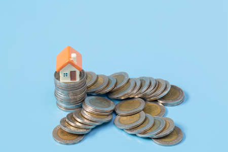 Mini house on stack of coins on a blue background. Concept of Investment property. Saving money, investing in real estate.