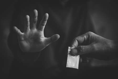 A black and white photo of Human hands stop drugs .  Stop drug addiction concept.