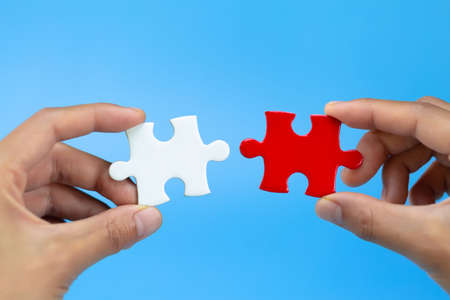 Two hands of businessman to connect couple puzzle piece. symbol of association and connection. business strategy. Imagens