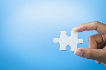 Hand holding jigsaw puzzleson a blue background, Business solutions, success and strategy concept. Imagens