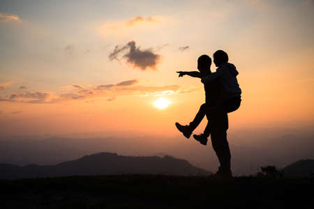 Couple on the mountain, Silhouette of happy couple  having fun over mountains background