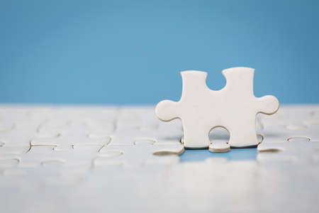 White jigsaw puzzle on a blue background. Completing final task, missing jigsaw puzzle pieces and business concept with a puzzle piece missing.