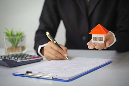 Real estate agent holding house model,  customer signing contract to buy house, insurance or loan real estate.