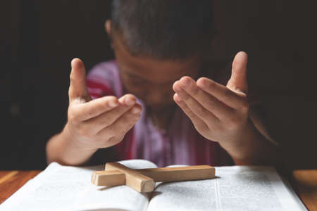 Soft focus on a Religious Christian Child  praying over Bible indoors, Religious concepts. prayer to god.