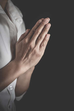Praying hands with faith in religion and belief in God on dark background. Pay respect.  Namaste or Namaskar hands gesture. 免版税图像