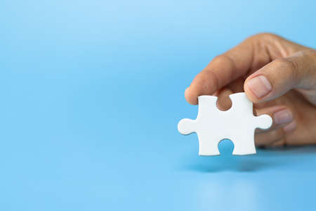 business woman hand holding  jigsaw puzzle piece, Business solutions, goals and strategy concepts.