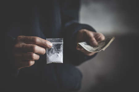 close up of addict with money buying dose, Purchase, possession and sale of drugs is punishable by law. drug trafficking,  addiction and sale concept. 免版税图像