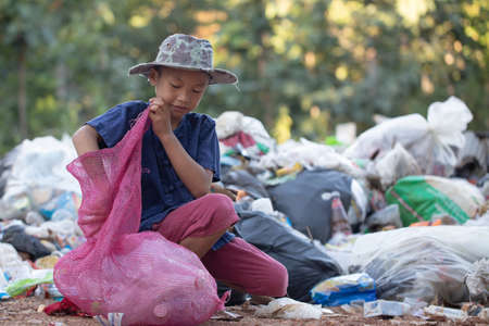 Poor boy collecting garbage in his sack to earn his livelihood, The concept of poor children and poverty 免版税图像