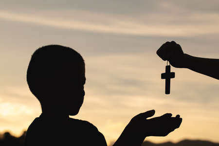Silhouette of a man praying with a cross in hand at sunrise,  religion concept.
