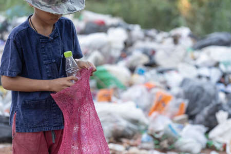 A poor boy collecting garbage waste from a landfill site in the outskirts, the lives and lifestyles of the poor, Child labor, Poverty and Environment Concepts 免版税图像