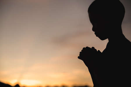A little prayer, A boy is praying seriously and hopefully to Jesus, Pay respect prayer concept for faith spirituality and religion. Religious beliefs Christian life crisis prayer to god.