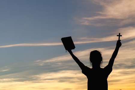 Women standing holding holy  bible for worshipping God at sunset background, Pray to the god, christian silhouette concept.