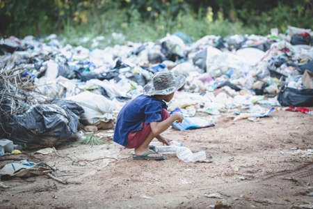A poor boy collecting garbage waste from a landfill site. Concept of livelihood of poor children.Child labor. Child labor, human trafficking, Poverty concept