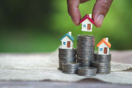 Woman's hand putting house model on coins stack. Concept for property ladder, planning savings money of coins to buy a home concept property mortgage and investment for a house. Standard-Bild