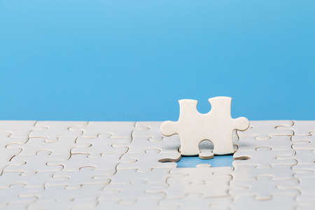 Unfinished white jigsaw puzzle on blue background with copy space. Business strategy teamwork and problem solving concept. Standard-Bild