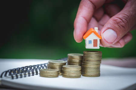 Woman's hand putting house model on coins stack. Concept for property ladder, planning savings money of coins to buy a home concept property mortgage and investment for a house.